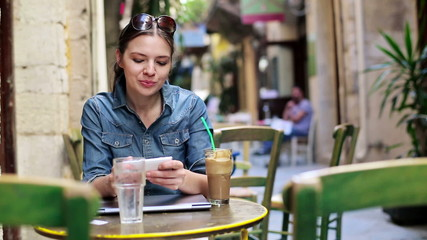 Pretty woman with smartphone sitting in cafe