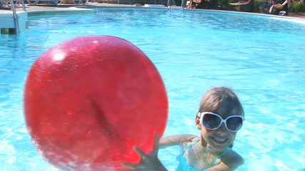 Child playing with beach ball in swimming pool.