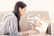 Woman using laptop with binary codes exploding over