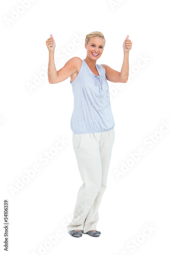 Blonde woman standing with thumbs up