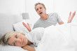 Man pleading with his upset partner in bed