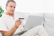 Man on his couch using laptop for online shopping