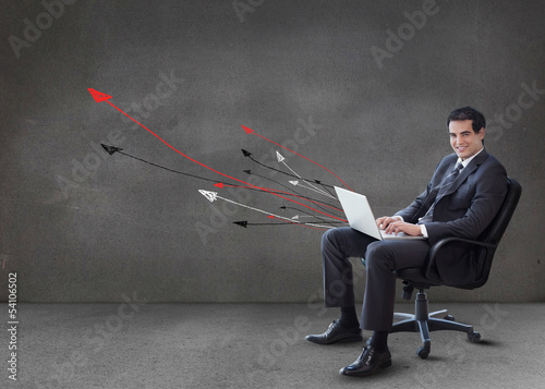 Businessman using his laptop arrows coming from it