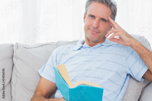 Man relaxing on his couch with a book looking at camera