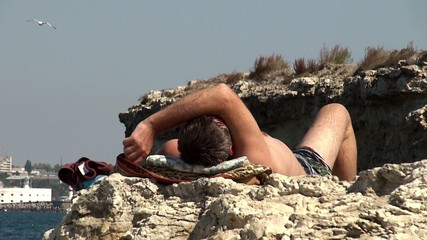 The guy sunbathing on a wild rocky beach.