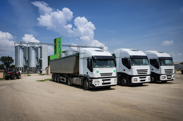 trucks parked in front of grain silos