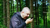 Man screaming in phone in forest