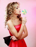 young happy woman with lollipop, isolated on pink background