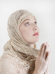 a girl who prays in the golden scarf on her head