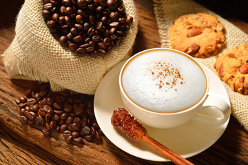 A cup of cappuccino with coffee beans and cookies