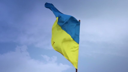 Ukrainian national flag waving on flagpole in blue sky. Ukraine