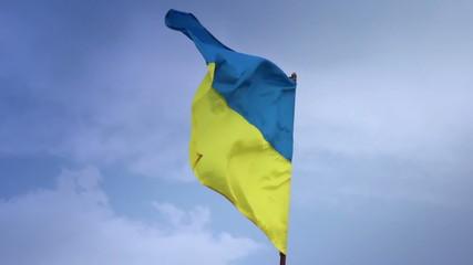 Ukrainian national flag waving on flagpole in blue sky. Ukraine