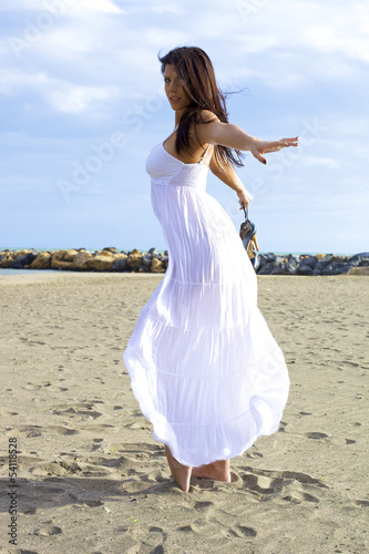 Beautiful woman posing and dancing on the sand