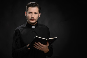 Priest with Holy Bible. Portrait of priest reading the Holy Bibl