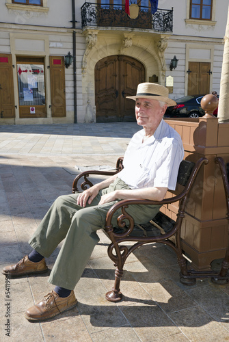 Senior man is resting on the square bench in sunny summer day.