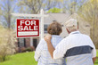 Senior Couple in Front of For Sale Sign and House