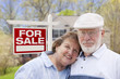 Retired Senior Couple Front of For Sale Sign and House