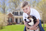 Playful Young Boy Hugs His Dog in Front of House