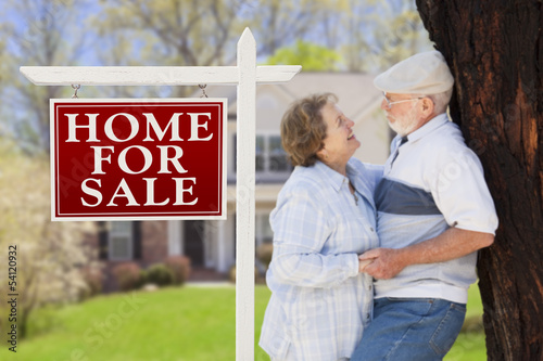 Affectionate Senior Couple Front of For Sale Sign and House