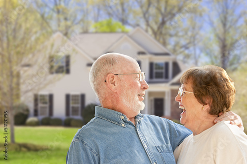 Happy Senior Couple in Front Yard of House