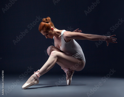 Graceful slender ballerina dancing in studio