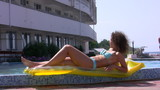 The young woman sunbathes near the water pool