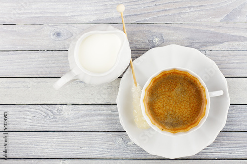 black coffee and cream jug on a wooden table