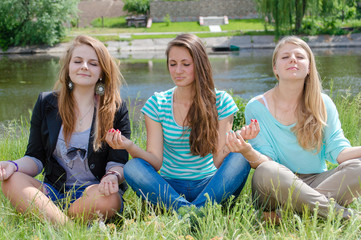 Three teen girls sitting in yoga position and meditating