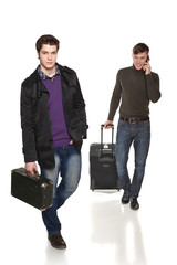 Two guys in full length traveling with suitcases