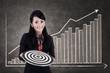 Businesswoman hold bull's eye on growing bar chart
