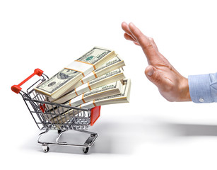 businessman's hand & shopping cart full of stacks of dollars