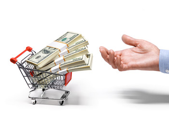 businessman's hand & shopping cart full of dollar banknotes