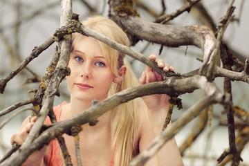 Frau schaut durch die Äste eines Baumes