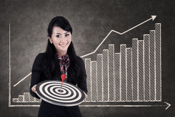 Businesswoman hold bull's eye on growing bar chart