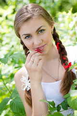 Young happy teen girl eating raspberry in garden