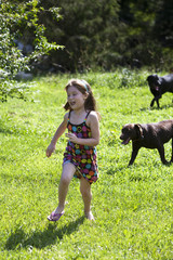 Young girl running from dogs