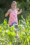 Young farm girl running through cornfield