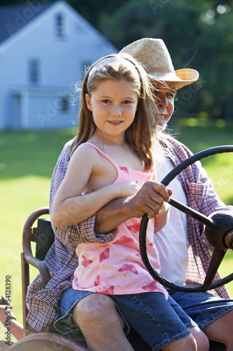 Young girl with grandfather driving a tractor on a farm