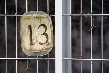 Parking place number thirteen on white wire fence