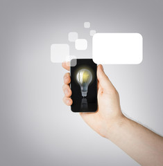 man hand holding smartphone with light bulb