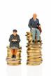 Rentner und Rentnerin auf Geldstapel