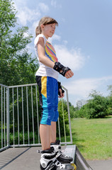Young girl poised at the top of a skating ramp