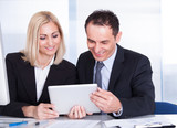 Businessman And Businesswoman Looking At Digital Tablet