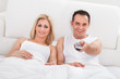 Couple Relaxing On Bed Watching Television
