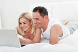 Happy Couple Lying On Bed Using Laptop