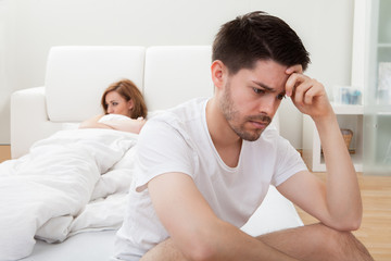 Depressed man sitting on the edge of the bed