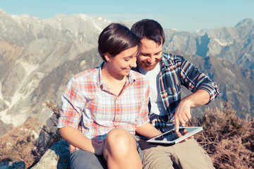 Couple with Digital Tablet at Top of Mountain