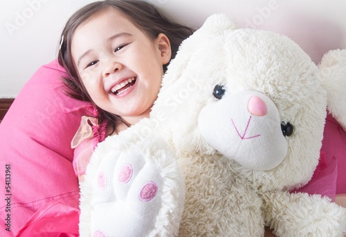 Girl laughing cuddling a soft toy bunny rabbit
