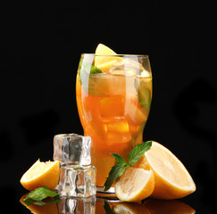 Iced tea with lemon and mint on black background