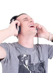 Close-up of a happy young man enjoying music with headphones